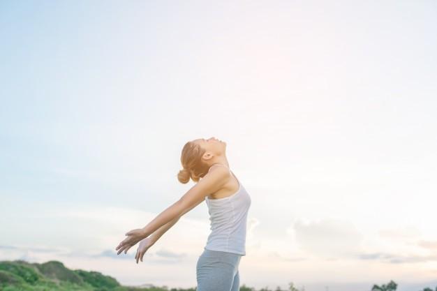 femme-concentree-etirant-ses-bras-fond-ciel_1150-376